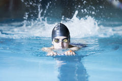 Swimmer swimming with a swim board. Male swimmer swimming with a swim board doing leg exercises in an indoor swimming pool - focus on the face Royalty Free Stock Images