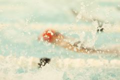 Backstroke Swim Abstract. A swimmer swims backstroke at a competition Royalty Free Stock Photos