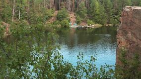 Swimmer swims in the lake. Water Quarry with rocky shores. stock video footage