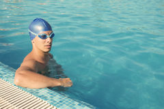 Swimmer. Taking a break at the pool edge Stock Photo