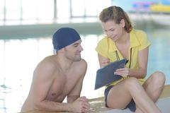 Swimmer talking to coach by poolside at leisure center Stock Photography