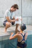 Swimmer talking to her coach poolside Stock Photography