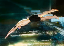 Swimmer teen boy diving fish style. Into the swimming pool Royalty Free Stock Photos