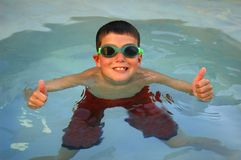 Swimmer Thumbs Up. Young boy giving thumbs up in pool royalty free stock images