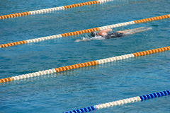 Swimmer training in pool. Lone swimmer training in lane of swimming pool Stock Photo