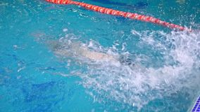 Swimmer during a workout in the pool. The swimmer trains in the pool and makes a turn and a rim and floats under the water stock video