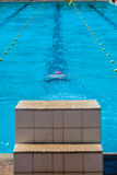 Swimmer Underwater Start Block. Swimmer male teenager with red cap has dived off start blocks under water to break surface and race Royalty Free Stock Image