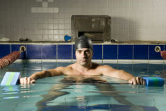 Swimmer with Weights. Male swimmer in swim cap holding weights while standing in pool. Horizontally framed photo Royalty Free Stock Photography