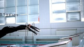 Swimmer in wetsuit dived into the pool. Slow motion stock footage