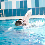 Swimmer woman performing the crawl stroke. Swimmer diving performing the crawl stroke Stock Photo