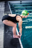 Swimmer woman about to dive into swimming pool Royalty Free Stock Image