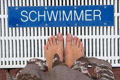 Swimmers. Legs standing in front of the Swimmer sign (Text is for swimmer, this is no logo or trademark Royalty Free Stock Image