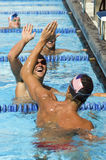 Swimmers High Fiving In Pool Royalty Free Stock Image
