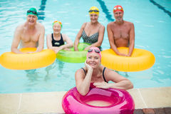 Swimmers with inflatable rings in pool. High angle view of swimmers with inflatable rings in pool Stock Image