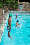 Swimmers jumping in swimming pool at leisure center. Little swimmers jumping in swimming pool at leisure center Stock Image