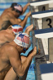 Swimmers Lined Up At Starting Blocks. Side view of male swimmers lined up at the starting blocks Royalty Free Stock Photography
