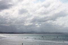 Swimmers out in grey ocean with waves on a stormy day. In Byron Bay Australia Stock Photo