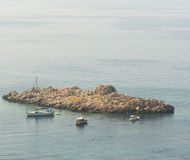 Swimmers and pleasure yachts near the stone island in the Bay of Petrovac, Montenegro Royalty Free Stock Image