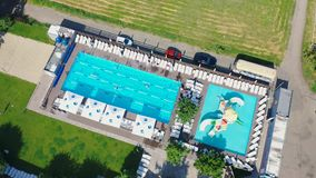 Swimmers of a private outdoor pool. Pool in the middle of the field, cars parked nearby stock video