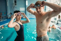 Swimmers puts on a goggles in swimming pool. Male and female swimmers puts on a goggles on workout in swimming pool. Aqua aerobics training, water sport Stock Photography