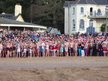 Swimmers ready for Christmas morning swim in Devon UK. Swimmers gather on the beach in Exmouth UK for the traditional Christmas Morning swim #Exmouth #Christmas Stock Photos