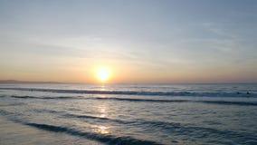 Swimmers in sea sunrise morning. Golden sunset ocean horizon. Sea waves blue water and orange sunlight. Beautiful landscape calm scenery. Serene tropical stock video footage