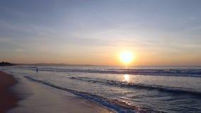 Swimmers in sea sunrise panning left. Golden sunset ocean horizon. Sea waves blue water and orange sunlight Beautiful landscape calm scenery. Serene tropical stock video footage