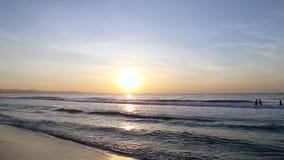 Swimmers in sea sunrise panning right. Golden sunset ocean horizon. Sea waves blue water orange sunlight Beautiful landscape calm scenery. Serene tropical stock footage