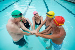 Swimmers stacking hands in pool Stock Images