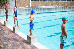 Swimmers standing on starting blocks at poolside Royalty Free Stock Photos