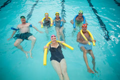 Swimmers swimming with pool noodles. Group of swimmers swimming with pool noodles Royalty Free Stock Images