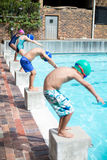 Swimmers taking position to jump in swimming pool Royalty Free Stock Photos