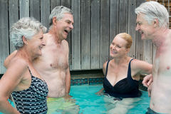 Swimmers talking while standing in swimming pool Stock Photo
