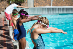 Swimmers with trainer ready to jump in pool. Little swimmers with trainer ready to jump in pool Stock Photography