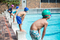 Swimmers waiting on stating blocks at poolside. Little swimmers waiting on stating blocks at poolside Stock Photos