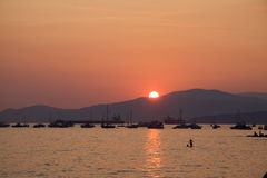 Swimmers in water as sun sets over English Bay, Vancouver. Boats and ships in the distance Royalty Free Stock Images