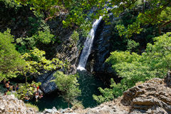 Swimmers at waterfall in forest Stock Photo