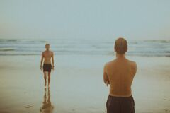 Swimmers on Wet Beach Stock Images