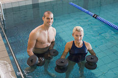 Swimmers working out with foam dumbbells in swimming pool at leisure centre. Portrait of fit swimmers working out with foam dumbbells in swimming pool at leisure Royalty Free Stock Photo