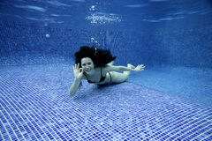 Swimming. Underwater picture of a woman smiling and signing with hands Stock Images