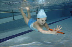 Swimming. Underwater picture of a young girl playing in the swimming-pool Stock Photos