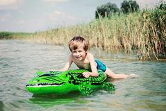 Swimming. 6 years old boy swimming in the water - kids royalty free stock photography