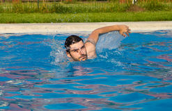 Swimming. Man swimming in the pool with water splashing royalty free stock images