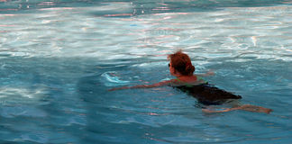 Swimming. Middle age woman  in swimming pool Royalty Free Stock Images