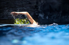 Swimming. Man swimming crawl in private pool with splash arm Royalty Free Stock Photos