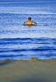 Swimming. Boy swimming in the sea water, beach visible in the foreground Stock Photo