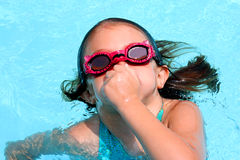Swimming. Young girl holding her nose as she prepared to go under water Royalty Free Stock Images