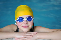 Swimming. Teenager on swimmingpool with blue googles and yellow bonnet Royalty Free Stock Photos