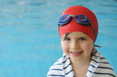 Swimming. Little girl with swimming googles and red bonnet Royalty Free Stock Image