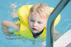 Swimming. Boys in life jacket swims in pool royalty free stock image